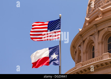 US and Texas flags flying over Texas State Capitol building Austin USA - Stock Photo