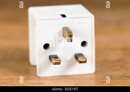 3 way plug adaptor 13 amp on wooden table top - Stock Photo