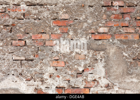 old building wall or brick background with pieces of old plaster - Stock Photo