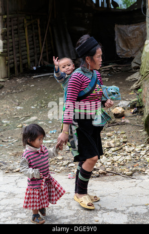 A mother and her two children in ethnic dress in Lao Chai Village near Sapa, Vietnam, Asia. - Stock Photo
