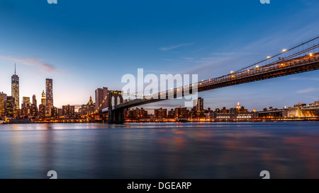 Brooklyn Bridge spanning the East River at dusk - Stock Photo