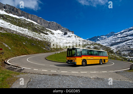 Yellow Swiss Post bus in a hairpin bend on the mountain road to the pass Klausenpass, Canton of Uri, Switzerland - Stock Photo