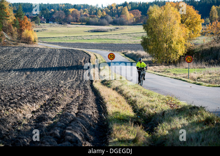 Bicycle rider struggling uphill on a countryside road in Sweden - Stock Photo
