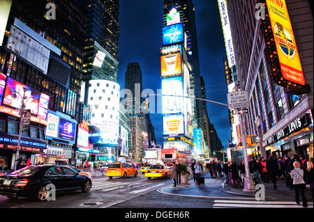 Lively Times Square by night in New York City, NY, USA - Stock Photo