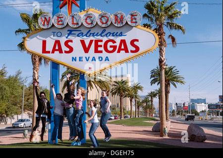 Tourists jumping at the iconic Welcome to fabulous Las Vegas Nevada sign - Stock Photo