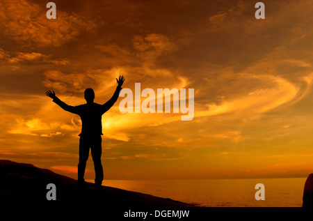 Silhouette of businessman standing on rock facing ocean open arms looking at the sky - Stock Photo