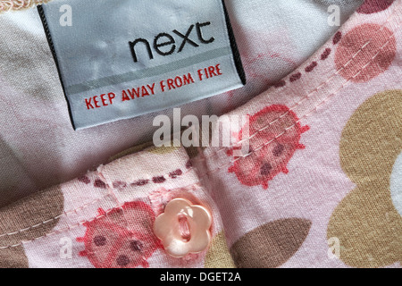 Next keep away from fire label in clothing - Stock Photo