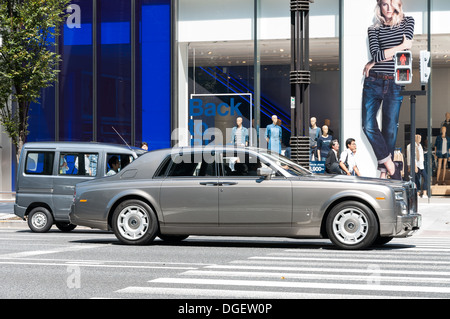 A Rolls Royce stops at a traffic light in the upscale district of Ginza in Tokyo, Japan. - Stock Photo