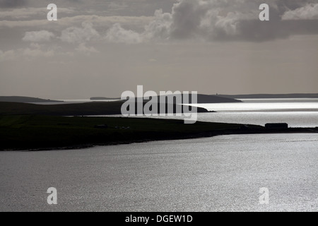Islands of Orkney, Scotland. Silhouetted view over the Orkney islands of Lamb Holm and Burray towards South Ronaldsay - Stock Photo