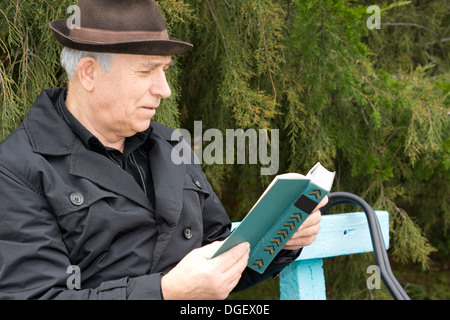 Senior gentleman relaxing reading his book outdoors sitting on a garden bench against greenery with a contented - Stock Photo