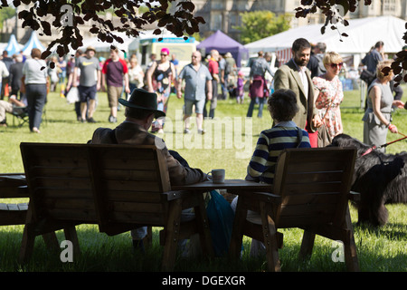 Couple taking break having drink in shade visitors walk around hot sunny Game Country Fair 2013 Burghley House Stamford - Stock Photo
