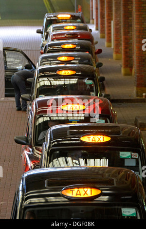 Queue of taxis inside London terminal station waiting for customers - Stock Photo
