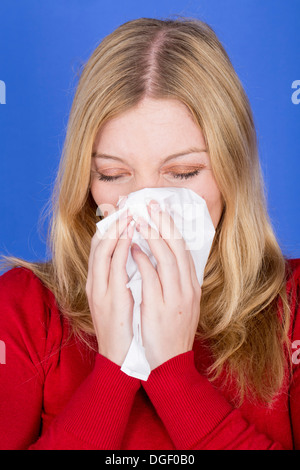 Model Released. Young Woman Blowing Nose - Stock Photo