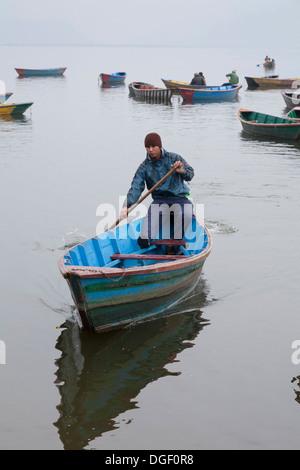 Young man paddling a boat on Phewa Lake - Pokhara, Pokhara Valley, Gandaki Zone, Nepal - Stock Photo