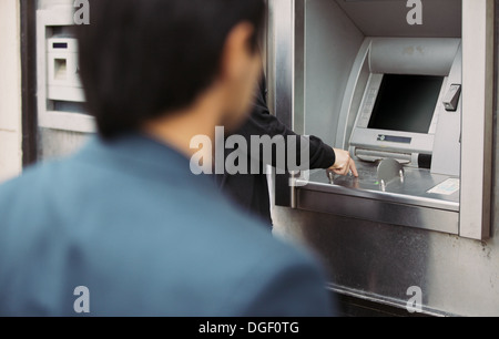 Man withdrawing cash at an ATM with a thief following him - Stock Photo