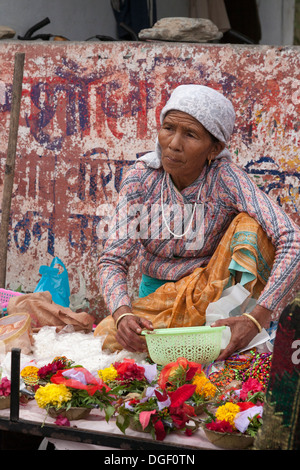 Mature woman selling offerings near Tal Barahi Temple on Phewa Lake - Pokhara, Pokhara Valley, Gandaki Zone, Nepal - Stock Photo
