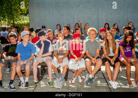 Middle school students listen to an outdoor lecture on appropriate campus behavior at the beginning of term. - Stock Photo