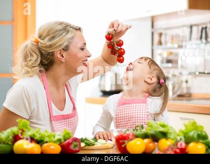 mother preparing dinner and feeding kid tomato in kitchen - Stock Photo
