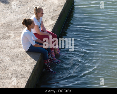 Two teenage girls sat on the edge of seapool dangling feet in the water, Bude, Cornwall, UK Stock Photo
