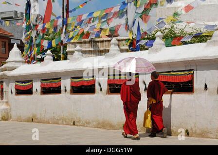 Two monks circling Boudhanath Stupa, Kathmandu, Nepal, Asia - Stock Photo