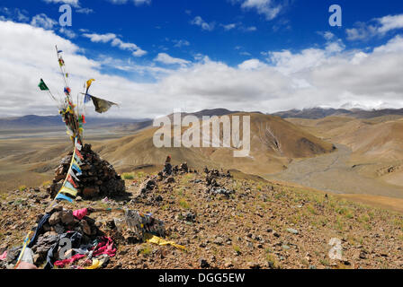 Stone cairn with prayer flags, Tingri plateau, snow-covered mountain tops under low clouds at back, Himalayas, Tibet, - Stock Photo
