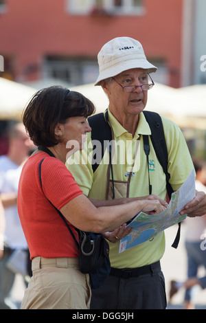 Couple of tourists map reading in Old Tallinn market square. Estonia - Stock Photo