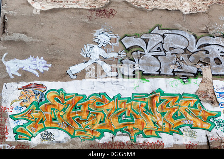 Street art and graffiti in Berlin on an old wall with cracked plaster - dog chasing man and tags - Stock Photo