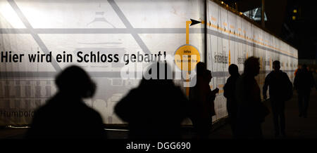 Berlin, Germany. 14th Oct, 2013. People walk in front of an illuminated advertising board for the Humboldt Forum - Stock Photo