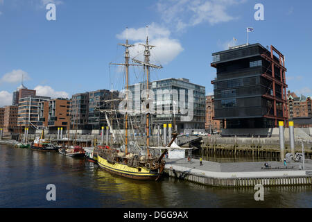 A historic tall ship is moored in the Tall Ship Harbour, Traditionsschiffhafen harbour, modern residential and office - Stock Photo