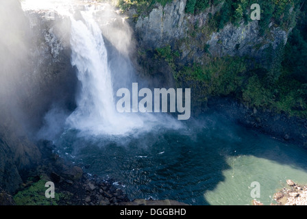 Water pouring over the top of Snoqualmie Falls waterfall into a natural river canyon, Washington State, USA - Stock Photo