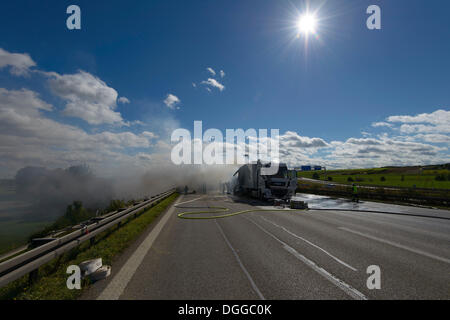 Firefighters extinguishing a truck fire on the A8 motorway near the 'Echterdinger Ei' junction, Stuttgart, Baden - Stock Photo