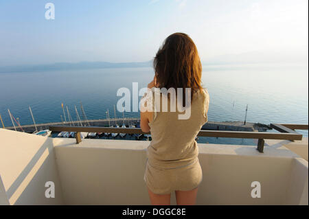 Young woman standing on a balcony, overlooking Lake Geneva, Meillerie, Évian-les-Bains, France, Europe - Stock Photo