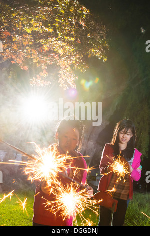 Girls with sparklers at night - Stock Photo