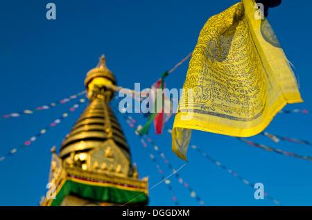 Yellow Buddhist prayer flag with Swayambhunath Stupa, Monkey Temple, Kathmandu Valley, Kathmandu, Kathmandu District - Stock Photo