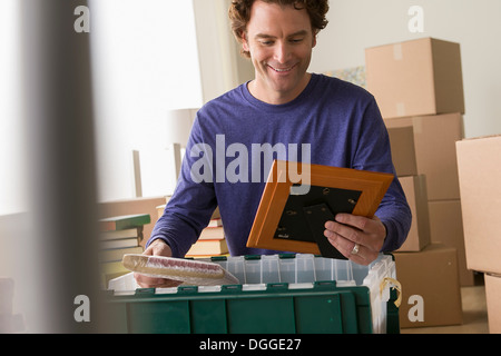 Mature man unpacking picture frame from crate - Stock Photo