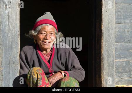 Old woman sitting in the doorway of a farmers house, Shivalaya, Solukhumbu District, Sagarmāthā Zone, Nepal - Stock Photo