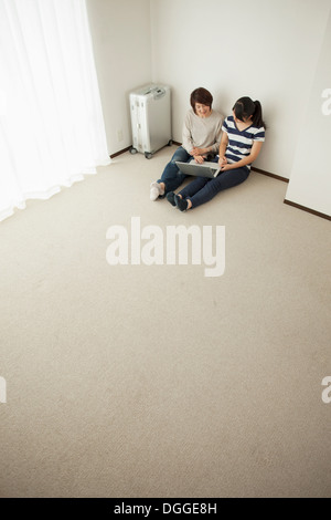 Mother and teenage daughter sitting on floor using laptop - Stock Photo