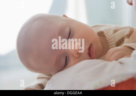 Baby boy sleeping on mother's shoulder, close up - Stock Photo