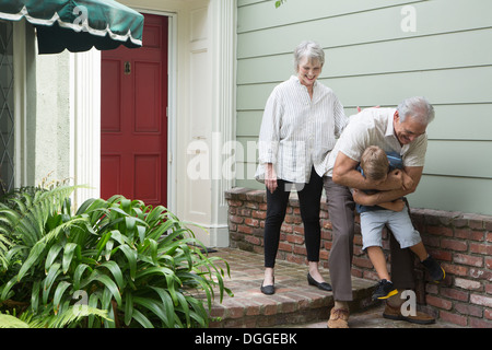 Senior man playing with grandson outside home - Stock Photo