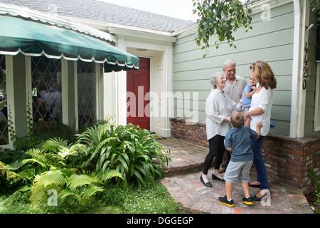 Senior couple greeting family at home - Stock Photo