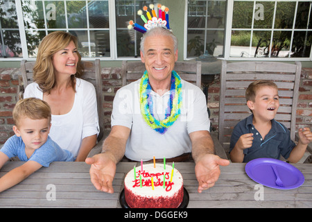 Senior man with birthday cake and family, portrait - Stock Photo