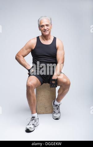 Senior man in sports clothing sitting in studio, portrait - Stock Photo