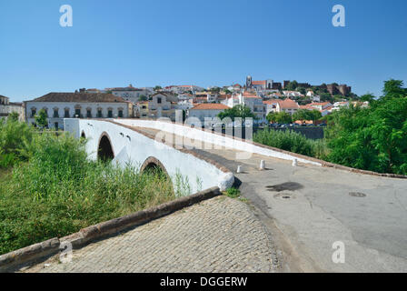 Old stone bridge crossing the Rio Arade river, in front of the historic town centre and the medieval castle of Castelo - Stock Photo