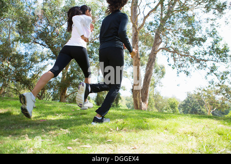 Young and mid adult woman jogging together - Stock Photo