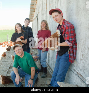 Farming family holding chickens, portrait - Stock Photo