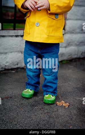 Close up of female toddler wearing yellow raincoat - Stock Photo