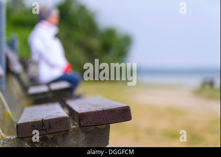 A woman sitting on a bench on the Baltic coast, Poel island, Mecklenburg-Western Pomerania - Stock Photo