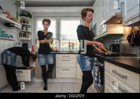 Young woman, depicted three times in the kitchen, Grevenbroich, North Rhine-Westphalia - Stock Photo