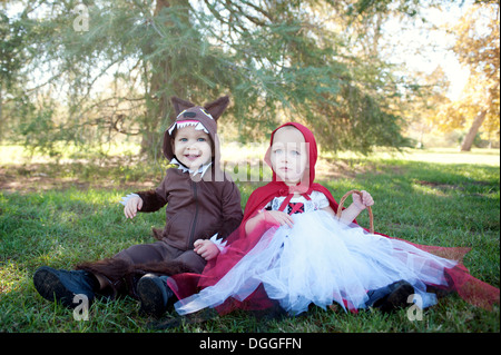 Toddler twins in woods dressed up as red riding hood and wolf - Stock Photo