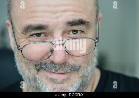 Smiling elderly man looking over his glasses, portrait, Grevenbroich, Rhineland, North Rhine-Westphalia, Germany - Stock Photo